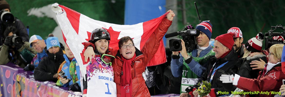 AbledPeople photo shows Canada's Alex Bilodeau dressed in his skiing gear celebrating his gold medal win in Men's Moguls at the Sochi Winter Olympics with his brother Frederic who is living with Cerebral Palsy. They are standing together with an arm around each other and holding a flag of Canada behind them with their other arms.