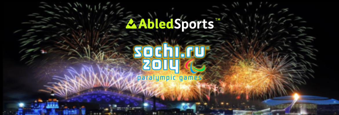 AbledSports Sochi Paralympics logo banner shows the logo over a slightly blurred image of fireworks above the Olympic site in Sochi, Russia.