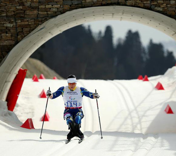 AbledSports photo from Sochi Paralympics site shows Ukraine's Lyudmila Pavlenko passing under a bridge arch as she races towards a gold medal in the Women's 12 kilometre Cross Country Ski Sitting at the Sochi Winter Paralympic games.