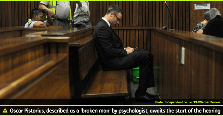AbledNews photo shows Oscar Pistorius sitting on the prisoner's bench in the North Gauteng High Court in Pretoria South Africa. He is dressed in a suit and tie and wearing glasses as he looks down at the smartphone he is browsing. The caption reads: Oscar Pistorius, described as a 'broken man' by psychologist, awaits the start of the hearing.