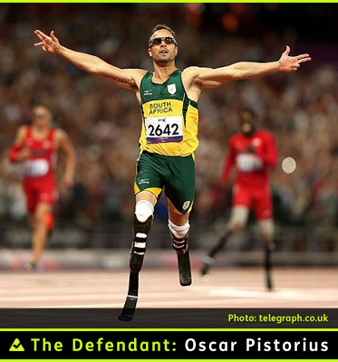 AbledPhoto shows The Defendant Oscar Pistorius winning a Paralympic race opn his carbon fibre prosthetic racing blades. His arms are spread wide as he crosses the finish line. he is wearing sport sunglasses and the reen and yellow track uniform of the South African team.