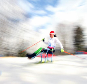 AbledSports photo from the Sochi Paralympics shows Liudmila Vauchok of Belarus competing in the women's 12km sitting cross-country skiing. She is wearing a red ski toque with white trim, a white jersey with green ski pants that have a white stripe down the side. She is strapped into a sitting double ski with her legs extended in front of her as she holds her orange ski poles with lime green and black ski gloves. The photo shows the surrounding trees and sky with a motion blur as she skis by.