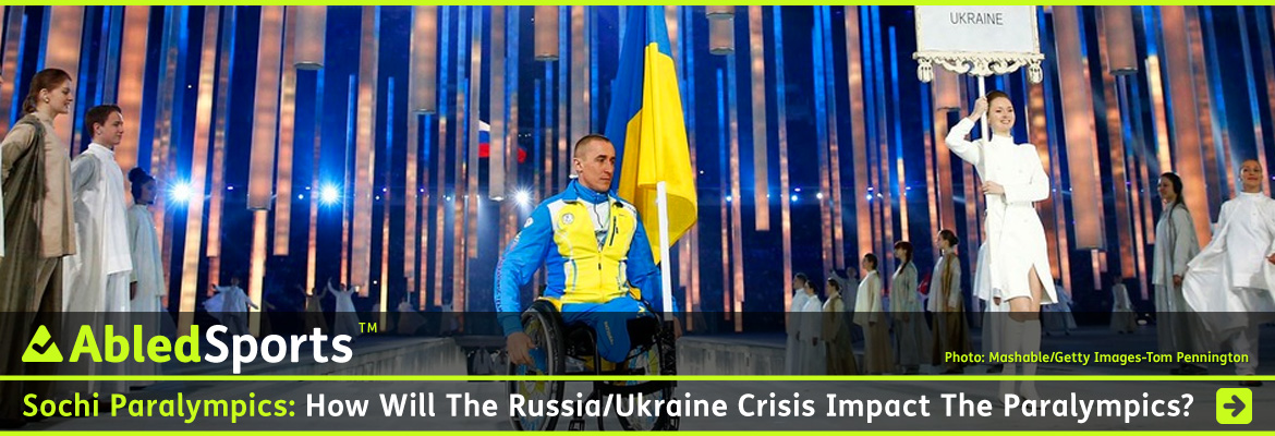 AbledSports Post Banner shows a photo of Biathlete Mikhaylo Tkachenko, the flag bearer for the Ukrainian Paralympic team wearing their blue uniform with a yellow torso, and with the blue and yellow flag of Ukraine mounted on his wheelchair as he enters the Olympic stadium in Sochi to thunderous applause during the opening ceremonies of the 2014 Sochi Winter Paralympic Games. The headline reads: Sochi Paralympics: How will the Russia/Ukraine crisis Impact the Paralympics?