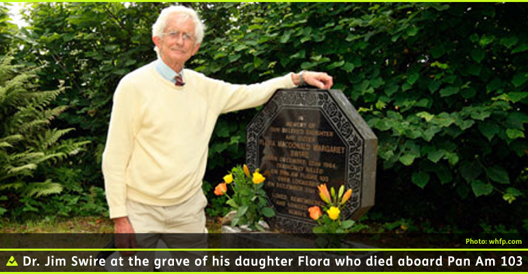 A Photo shows Dr. Jim Swire kneeling beside the gravestone of his Daughter flora who died in the bombing of Pan Am Flight 103 over Lockerbie, Scotland. Dr. Swire has white hair and is wearing glasses, a blue dress shirt with a red and gold striped tie under a yellow sweater with khaki slacks. He is resting his left arm on the top of the octagonal black and brown granite headstone. Photo from the West Highland Fee Press. Click here to go to their August 2013 profile of Dr. Swire.
