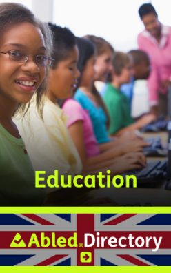 AbledLondon Education Directory link banner shows senior elementary school students sitting side by side at a bank of computers with their teacher in the background. The female student in the foreground wears glasses and is smiling at the camera. The AbledDirectory logo is shown in the lower third against a Union Jack background. Click here to go to the AbledLondon Education Directory.