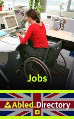 The AbledLondon Jobs Directory Link banner shows a woman wearing a red long-sleeve cardigan shirt with grey slacks sitting in a wheelchaire with burnt-orange wheel rims whicle working at the computer on her desk next to a window. The AbledDirectory logo is shown in the lower third against a Union Jack background. Click here to go to the AbledLondon Jobs Directory.