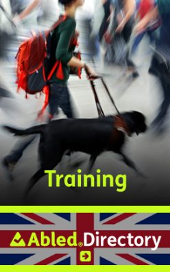 The AbledLondon Training Directory shows a teenager from the neck down walking with a black labrador guide dog through a blurred background of pedestrians inside a building while wearing a large red backpack. The AbledDirectory logo is shown in the lower third against a Union Jack background. Click here to go to the AbledLondon Training Directory.
