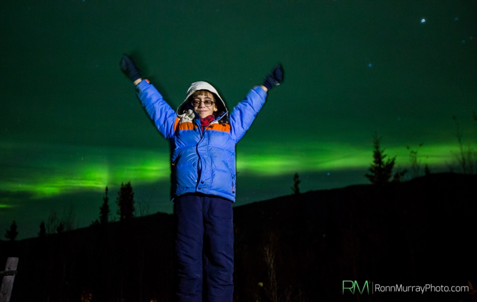 Photo by RonnMurrayPhoto.com shows 9 year-old Ben Pierce standing with his arms outstretched with the Northern Lights casting a green hue in the sky in the background. Ben is wearing a blue parka with and orange stripe and ivory hood. He wears tinted glasses and is smiling at the camera. Click here to go to RonnMurrayPhoto.com