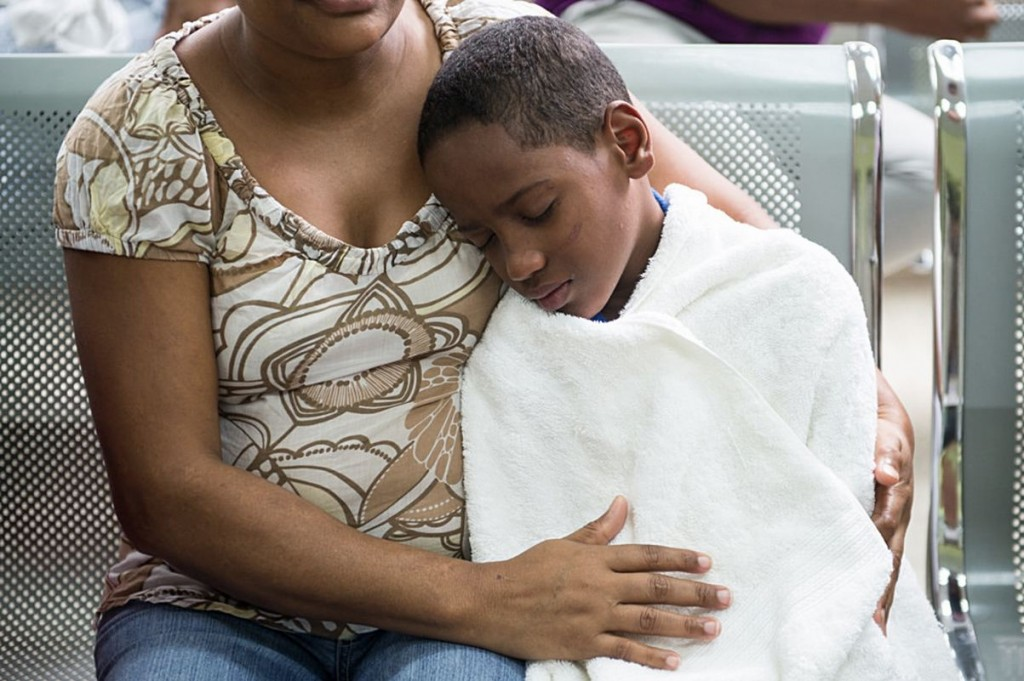Photo from the Pan American Health Organization shows a young boy wrapped in a white towel leaning against his mother as they si in the waiting area of a hospital in Santo Domingo in the Dominican Republic. This series of photos bny Luz Sosa shows the physical pain many patients feel after the onset of symptoms of Chikangunya.