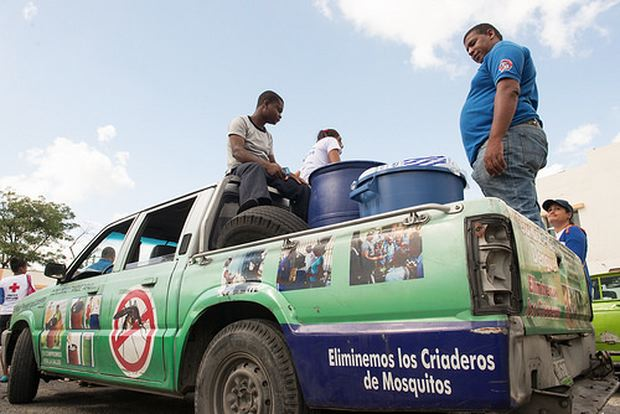 Photo by Luz Sosa shows a white pickup truck of the Ministry of Health with a banner 'skin' attached that depicts photos as well as an image of a mosquito with a red circle with a titled bar, meaning 'no' and other preventative information as part of a 'National Day Against Chikungunya' in the Dominican Republic.