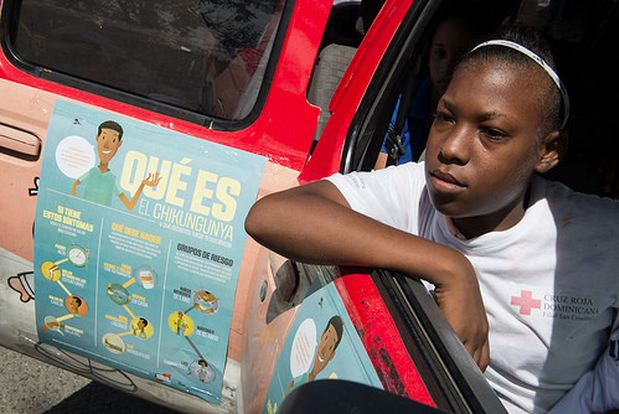 Photo by Luz Sosa shows a teenage girl sitting and resting her right arm on the open door window of the white pickup truck of the Ministry of Health with a banner 'skin' attached that depicts photos of mosquitoes along with illustrations about prevention measures as part of a 'National Day Against Chikungunya' in the Dominican Republic.