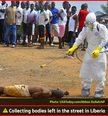 AbledALERT photo shows a health worker in protective medical gear spraying the body of a suspected dead Ebola victim that's been dumped in the street in Monrovia, Liberia as a crowd of people looks on.