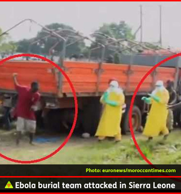 AbledALERT-photo shows healthcare workers in Sierra Leone being confronted by a man who is raising one arm with a large stone and he holds another large rock in his hand. The caption reads: Ebola burial team attacked in Sierra Leone.