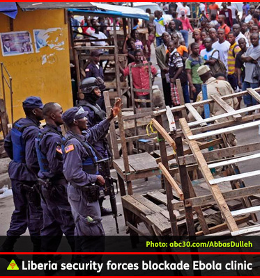 AbledALERT photo shows security forces in Liberia setting up a barricade of chairs and wooden shelving to blocked an Ebola treatment center from a crowd on the street.