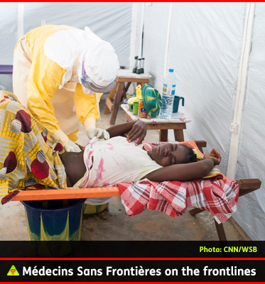 AbledALERT Photo shows a Doctor from Médecins Sans Frontières or Doctors Without Borders treating a female patient in West Africa. The doctor is dressed in a hello protective suit with white protective head gear as he bends over the patient.