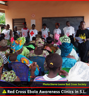 AbledALERT photo shows Red Cross Volunteers in Sierra Leone providing an awareness class on Ebola at a community school in an outdoor classroom where local people are attending.