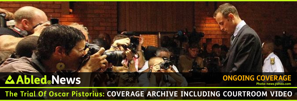 AbledNews-post banner shows a side view of Oscar Pistorius facing a bank of press cameras in the Gauteng High Court in Pretoria, South Africa. He is wearing a suit and tie and is dtanding with his head bowed and his hands clasped in front of him.