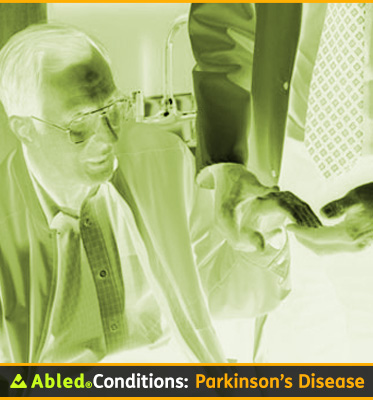 AbledConditions: Parkinson's Disease: Photo shows a doctor holding a male patient's hand to test for shakiness and strength. The image is inverted and looks like an X-ray in a green tone that matches the green of the Abled logo.