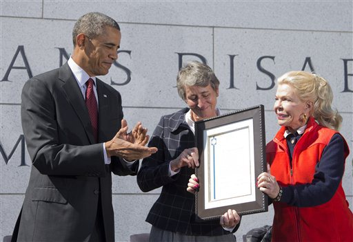 President Barack Obama, left, is presented a plaque by philanthropist Lois Pope, right, and Secretary of the Interior Sally Jewell, during the American Veterans Disabled for Life Memorial dedication ceremony in Washington, Sunday, Oct. 5, 2014. President Obama paid tribute to disabled U.S. veterans on Sunday, pointing to the dedication of a new memorial honoring those severely injured in war as a symbol of the nation's perseverance and character. (AP Photo/Manuel Balce Ceneta)