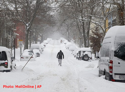 Image of man walking down snow covered street in the Georgetown area of Washington DC.