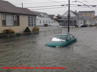 Photo shows a car underwater to its headlights in floodwaters flowing through North Wildwood, New Jersey.