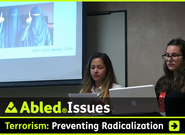 AbledIssues: Terrorism: Preventing Radicalization. Image: Photo shows two female forensic psychologists making a presentation on the subject. A photo of two women wearing burqas is project on the screen behind them.