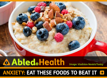 AbledHealth: Anxiety-Eat-these-foods-to-beat-it. Image:A bowl of oatmeal porridge with blueberries, raspberries and sliced almonds on top.