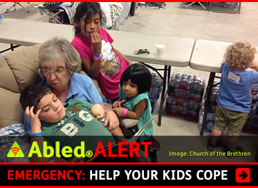 AbledALERT: Emergency: California WIldfires: Help your kids cope. Image: An elderly woman volunteer from the Church of the Brethren comforts children at an evacuation center during the California wildfires.