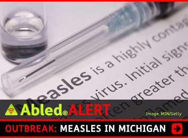 AbledALERT: Outbreak: Measles in Michigan. Image: Photo of a vaccine vial and a syringe placed on a book page that explains Measles is a highly contagious virus.