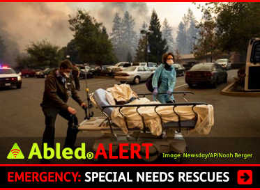 AbledAlert: Emergency: Special Needs Rescues. Image: Medical personnel evacuate patients as the Feather River Hospital burns while the Camp Fire rages through Paradise, California. A patient is wrapped in sheets on a hospital bed/gurney as they're being wheeled to an ambulance.