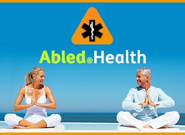 AbledHealth Box. Image: Middle aged man and woman sit cross-legged on cushions smiling in a meditative pose with the ocean in the background.
