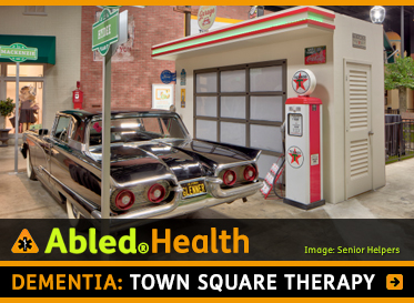AbledHealth: Dementia: Town Square Therapy. Image: A vintage Thunderbird auto is parked at a mock-up 1950's style gas station in an indoor Town Square.