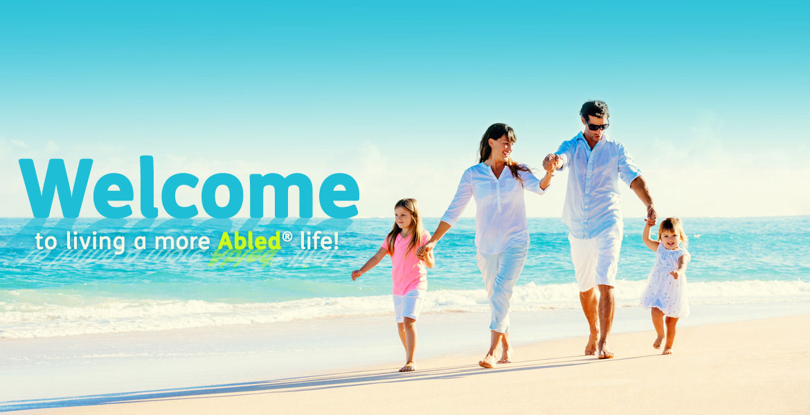 "Abled.com: Welcome to living a more Abled life! Photo shows a mother and father with two young girls walking along a sandy beach with the welcome text ""floating on the water"" in the background."