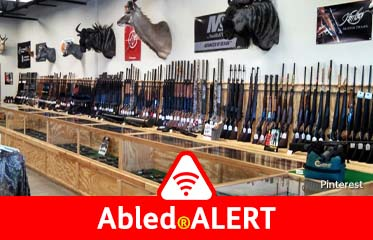 Abled.ALERT: Photo of rifles lining a wall under stuffed wild game heads, and. above handgun cases in a gun store.
