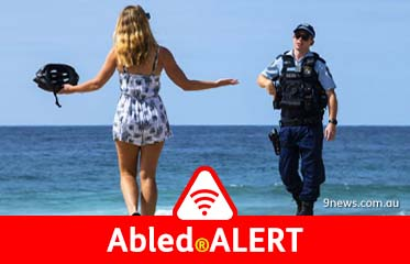 Abled.ALERT: Photo of a woman holding her arms wide as she questions a police officer at Maroubra Beach in Australia as it's being closed down.