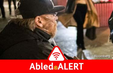 Abled.ALERT: Photo of a man in a motorized wheelchair wearing an oxygen tube in San Francisco.