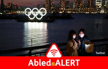 Abled.ALERT: Photo: Two young women take a selfie with the lighted Olympic Rings lit-up at night while floating on a barge in Tokyo Bay behind them.