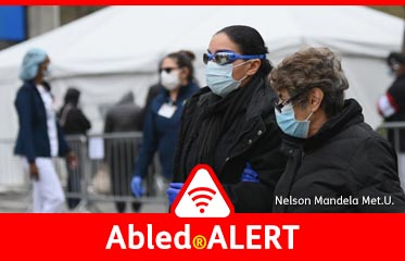 Abled.Alert: Photo shows people wearing masks and goggles pass by a COVID-19 screening tent outside the Brooklyn Hospital Center on March 20, 2020 in the Brooklyn borough of New York.