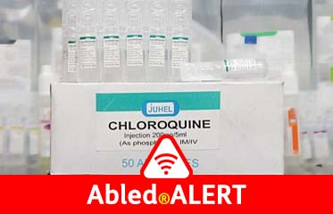 Abled.ALERT: Photo of a box of Chloroquine injection ampoules with a bunch of the ampoules stacked on top of the box in a lab.