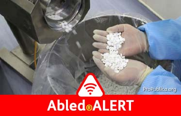 Abled.ALERT: Photo of factory worker in protective gear holding scooped tablets in both gloved hands as a machine deposits them into a plastic lined collection pail.