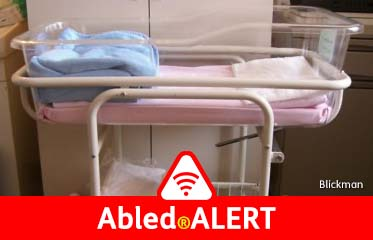 Abled.ALERT: Photo of a side view of a clear plastic infant hospital bassinet nestled in a tubed metal frame.