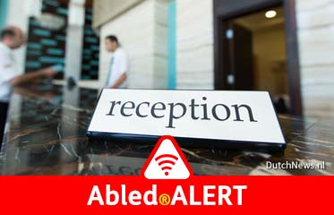 """Abled.ALERT: Photo shows a """"Reception"""" sign floating in the foreground with a blurred image of a customer checking in at a hotel front desk inn the background."""
