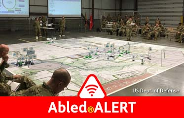Abled.ALERT: Photo shows the camp-clad members of the Joint Task Force - Civil Support (JTF-CS) conducting a Rehearsal of Concept (ROC) drill practicing deployment and objectives on top of a large map of their target disaster site spread out on a floor in front of two large monitors.
