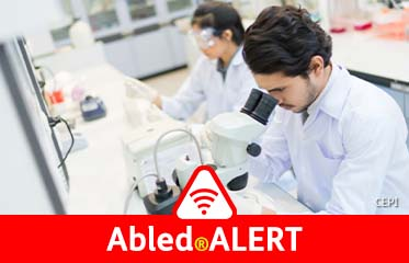 Abled.ALERT: Photo of a male researcher looking into an electron microscope as a female researcher wears protective goggles in the background while she works with lab samples at the Pasteur Institute.