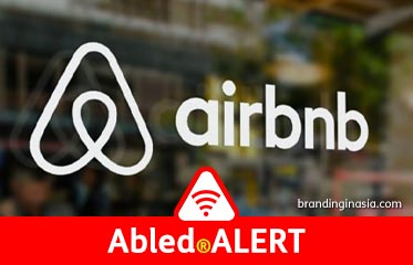 Abled.ALERT: Photo of airbnb logo on a window with the office background out of focus.