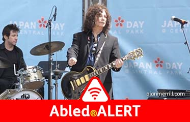 Abled.ALERT: Photo of Alan Merrill performing at a Japan Day concert. He has long flowing hair and is playing a black Les Paul electric guitar.
