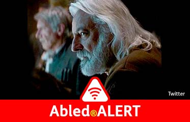 Abled.ALERT: Photo of British actor and dialect coach Andrew Jack with long-flowing white hair and a beard sitting on the set of a Star Wars movie with Harrison Ford in the background.