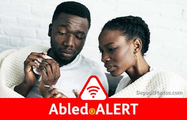 Abled.ALERT: Stock photo of an African-American couple. The man holds a tissue, while the woman checks a thermometer.