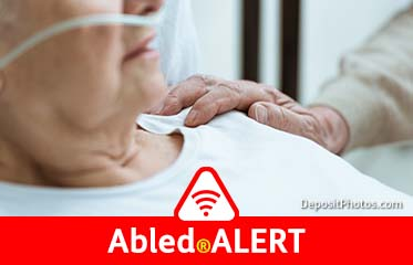 Abled.ALERT: Stock photo of an elderly man with a nasal oxygen cannula and gown in bed while his wife places a hand on his shoulder.