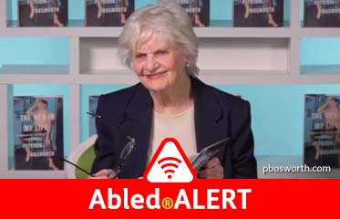 "Abled.ALERT: Video still-frame of actress and author Patricia Bosworth smiling as she sits at a desk at a book signing for her memoir ""The Men in my Life"". hardcover volumes stand upright on shelving behind her."